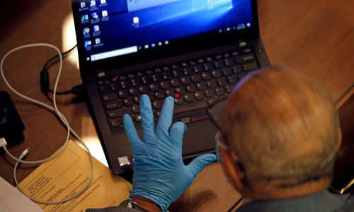 A man wearing gloves and using a laptop.